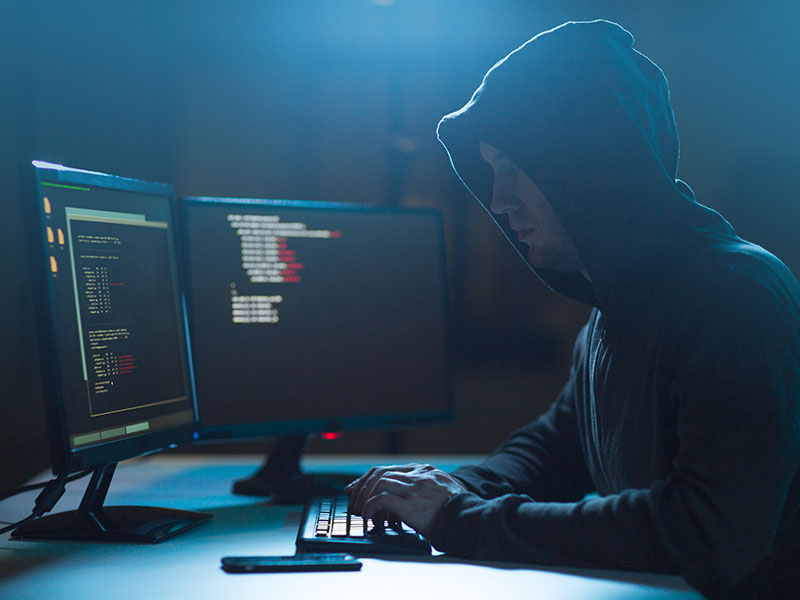 Hacker in a hoodie writing code